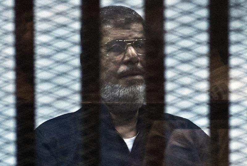 Egypt's ousted president Mohamed Morsi stands behind bars during his trial in Cairo, on June 16, 2015 (AFP Photo/Khaled Desouki)