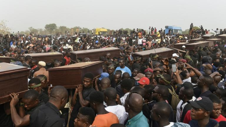 Pall bearers carry coffins during the funeral service for people killed during clashes between cattle herders and farmers