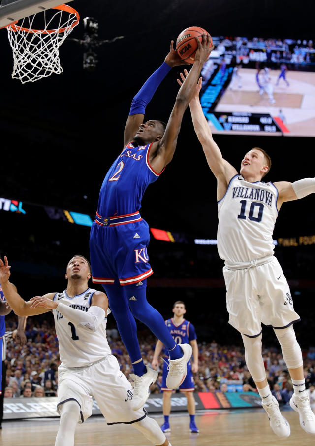 Kansas guard Lagerald Vick (2) drives to the basket between Villanova's Jalen Brunson (1) and Donte DiVincenzo (10) during the first half in the semifinals of the Final Four NCAA college basketball tournament, Saturday, March 31, 2018, in San Antonio. (AP Photo/David J. Phillip)
