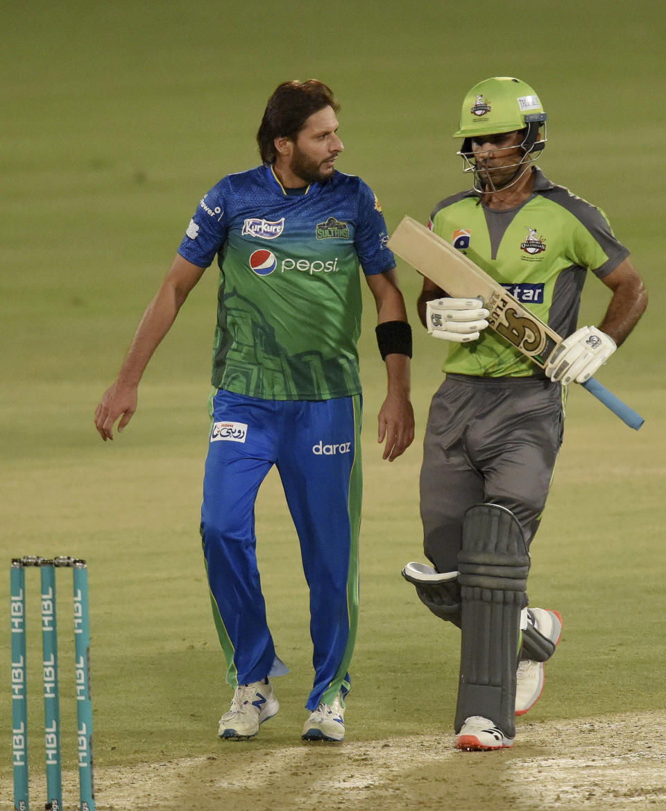 Multan Sultans spinner Shahid Afridi, left, chats with Lahore Qalandars batsman Fakhar Zaman during the second eliminator cricket match of Pakistan Super League T20 cup at National Stadium in Karachi, Pakistan, Sunday, Nov. 15, 2020. (AP Photo/Fareed Khan)