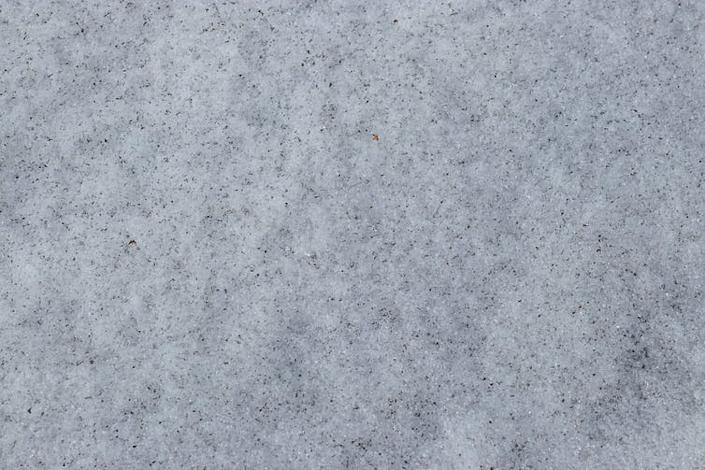 Ice surface with black stain from soot.