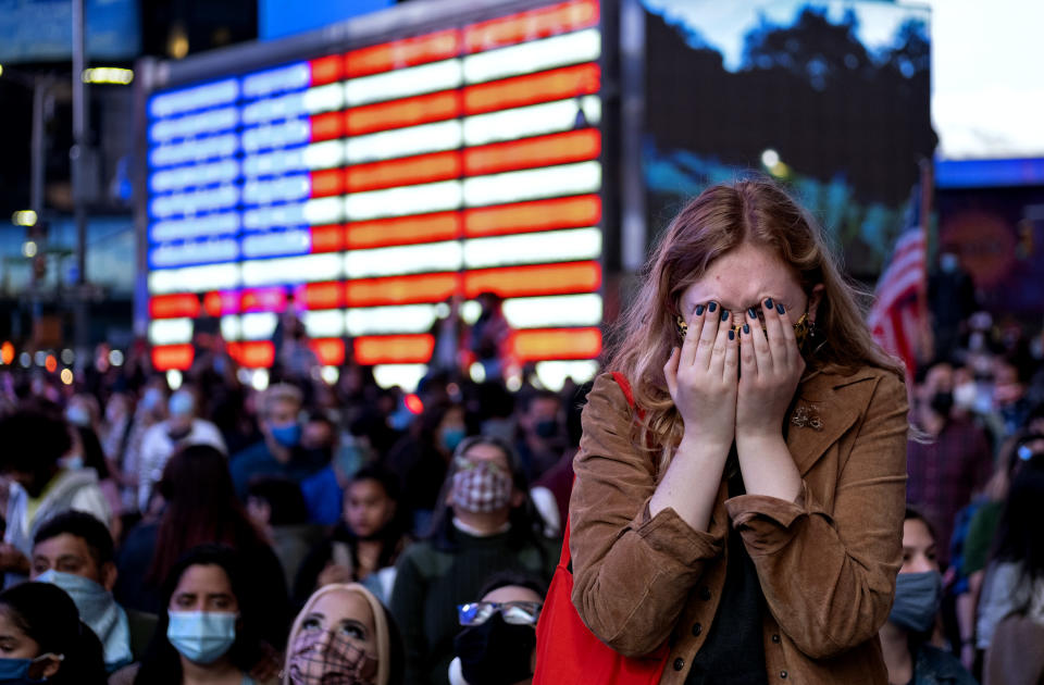 Fletcher Peters of New York, a journalism student at NYU, reacts as she watches President-elect Joe Biden on a monitor in Times Square on Saturday, Nov. 7, 2020, in New York, as he addressed the nation. (AP Photo/Craig Ruttle)