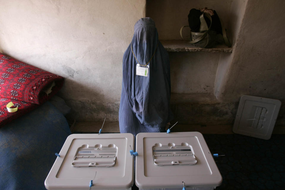 A woman poll worker waits for voters to arrive at a polling station in Kandahar, Afghanistan, Sept. 18, 2005. Afghanistan held landmark parliamentary elections, the first in three decades. (AP Photo/Saurabh Das)