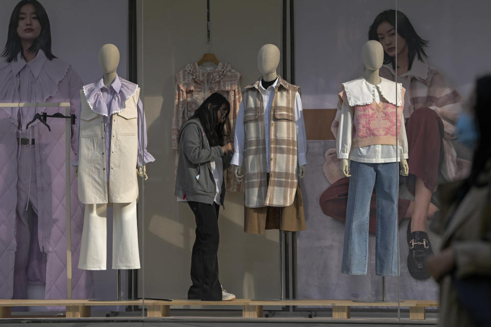 An employee adjusts autumn and winter season clothings on the mannequins on display at a fashion boutique in Beijing, Wednesday, Oct. 13, 2021. China's import and export growth slowed in September amid shipping bottlenecks and other disruptions combined with coronavirus outbreaks. (AP Photo/Andy Wong)