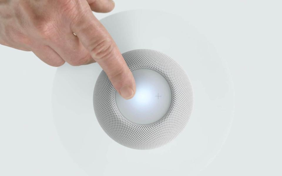 A finger reaches out to touch a little speakerball - Apple