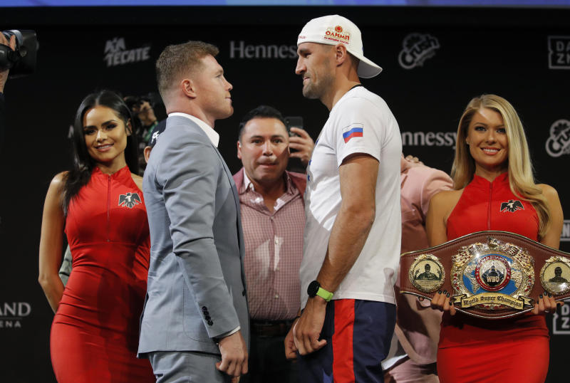 Sergey Kovalev, center right, and Canelo Alvarez pose for photographers during a news conference Wednesday, Oct. 30, 2019, in Las Vegas. The two are scheduled to fight in a WBO light heavyweight title bout Saturday in Las Vegas. (AP Photo/John Locher)