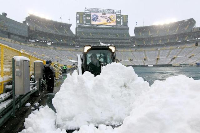 Green Bay Packers grounds crew members work to clear snow from the turf at Lambeau Field, where the team has asked for up to 700 people to help shovel snow from the stands ahead of Sunday's NFL playoff game against Seattle (AFP Photo/Dylan Buell)