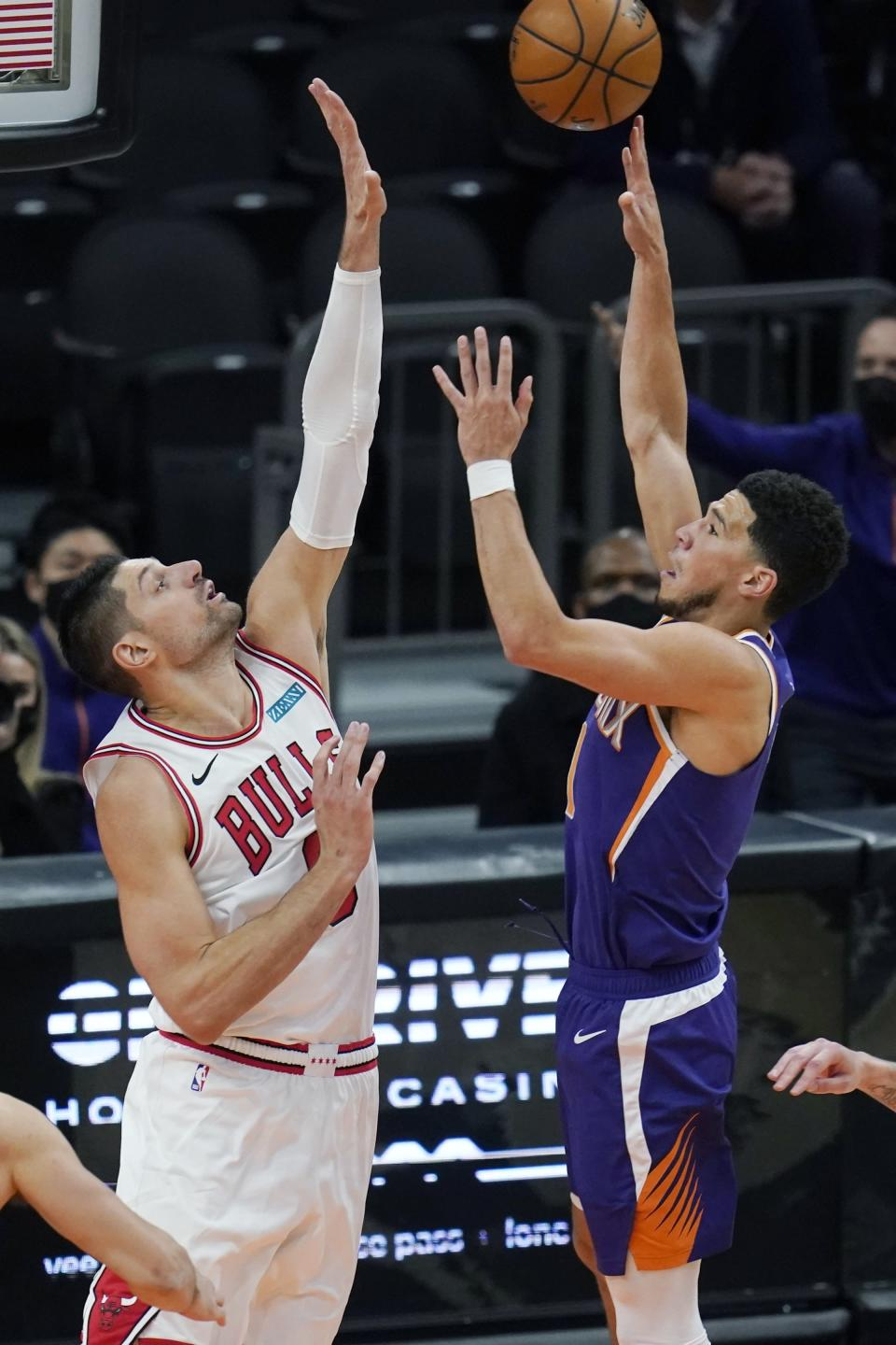 Phoenix Suns guard Devin Booker, right, shoots over Chicago Bulls center Nikola Vucevic during the second half of an NBA basketball game Wednesday, March 31, 2021, in Phoenix. (AP Photo/Ross D. Franklin)