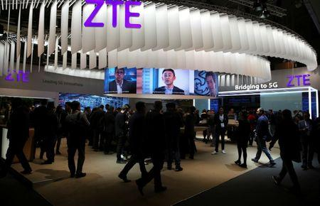 FILE PHOTO: People stand at ZTE's booth during Mobile World Congress in Barcelona