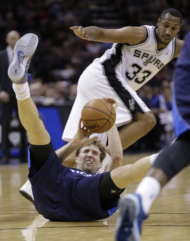 Dallas Mavericks' Dirk Nowitzki, bottom, of Germany, falls to the floor as he and San Antonio Spurs' Boris Diaw (33), of France, chase a loose ball during the first half of Game 2 of the opening-round NBA basketball playoff series on Wednesday, April 23, 2014, in San Antonio. (AP Photo/Eric Gay)