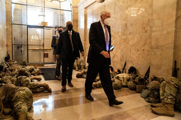 House Majority Leader Steny Hoyer walks past members of the National Guard sleeping in the halls of Capitol Hill on January 13, 2021. / Credit: Kent Nishimura / Los Angeles Times via Getty Images