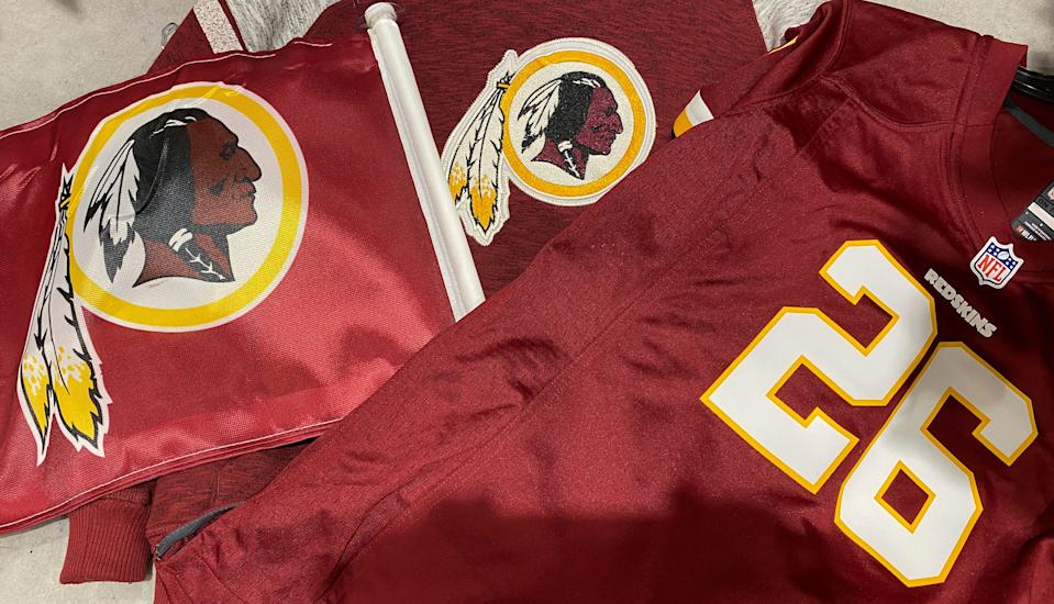 Washington Redskins football shirts and a team flag on sale at a sporting goods store in Bailey's Crossroads, Virginia, U.S., June 24, 2020.  REUTERS/Kevin Lamarque