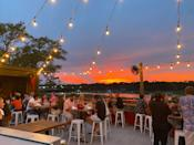 """<p><strong>Give us an overview.</strong> If you take just a ten minute drive from downtown, you'll be rewarded with a pleasing change of scenery. This tavern trades urban rooftops for pastoral river views from its roof deck, with the panoramic greenery of Shem Creek laid out before guests. The deck itself has a modern rustic aesthetic, with simple but comfortable wooden and wrought iron furniture and an open design that shows off the sunsets to full effect. It's a welcoming, unpretentious spot that makes the most of its bucolic setting.</p> <p><strong>How's the crowd?</strong> The crowd here skews slightly more mature, the short drive out means fewer boozy bachelorette parties and more couples just looking for a relaxed terrace. People here are mostly happy just to gaze out over the riverside scenery and enjoy the reds and oranges of the sunsets each evening.</p> <p><strong>How are the drinks?</strong> The cocktail menu is solid, varied, and doesn't stray into any arcane territory. There are good iterations of the classics—margaritas, palomas, mojitos—bolstered by a few house creations. A cucumber mint cooler seems like a perfect start to a warm Charleston evening, while the Mocha Peppucino will appeal to sweet-toothed drinkers. The wine cellar provides a good choice of American favorites, and the beer and spirits lists both benefit from local brewery and distillery offerings.</p> <p><strong>What do they have on the food menu?</strong> The deck is limited to a dedicated sushi menu. There's a selection of familiar rolls such as spicy tuna, fresh crab, and California, and left field innovations such as their Sweet Potato Roll. The seafood is wonderfully fresh, as you might expect from this corner of the world.</p> <p><strong>Did the staff do you right?</strong> With clientele volume lower than many of the <a href=""""https://www.cntraveler.com/gallery/best-bars-in-charleston?mbid=synd_yahoo_rss"""" rel=""""nofollow noopener"""" target=""""_blank"""" data-ylk=""""slk:downtown bars"""" class="""""""