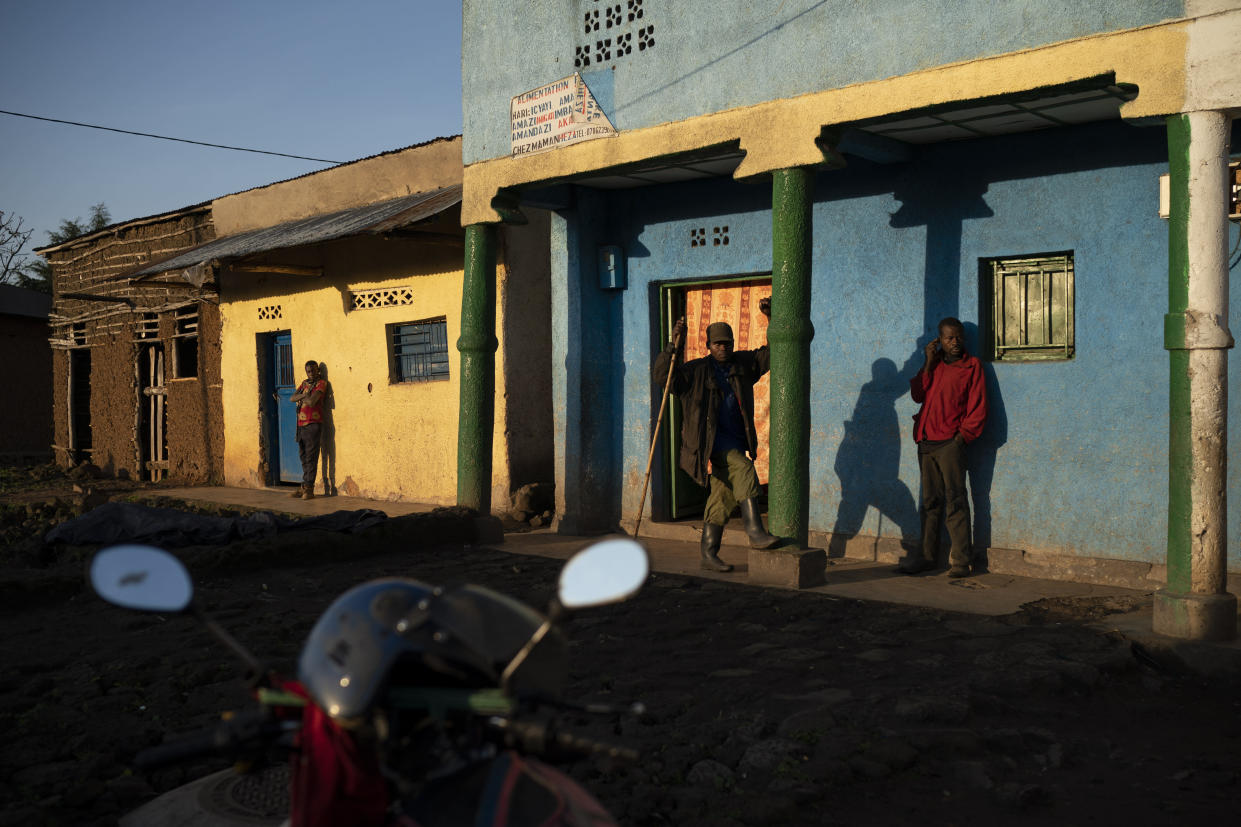 Residents stand outside buildings as the sun rises in Kinigi, Rwanda. (Photo: Felipe Dana/AP)