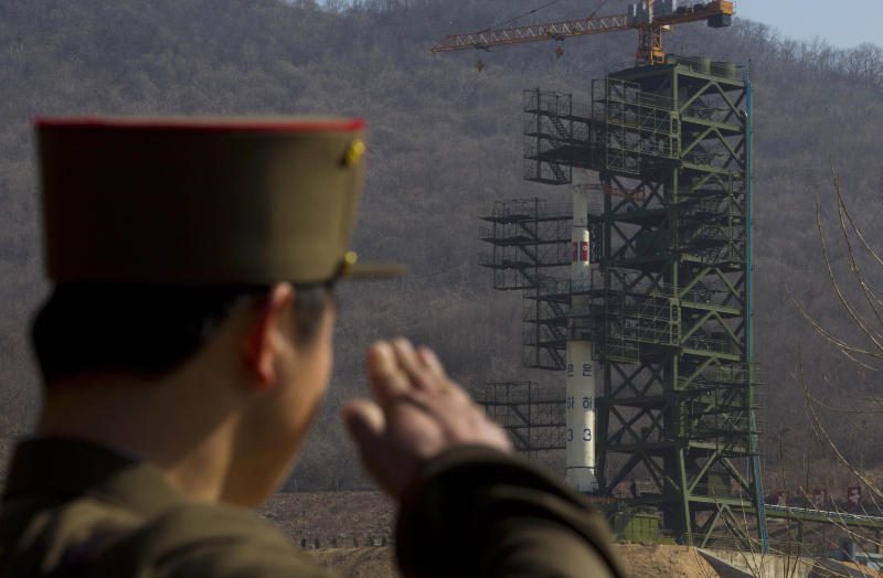 A North Korean soldier salutes in front of the country's Unha-3 rocket, slated for liftoff between April 12-16, at Sohae Satellite Station in Tongchang-ri, North Korea on Sunday April 8, 2012. North Korean space officials have moved a long-range rocket into position for this week's controversial satellite launch, vowing Sunday to push ahead with their plans in defiance of international warnings against violating a ban on missile activity. (AP Photo/David Guttenfelder)