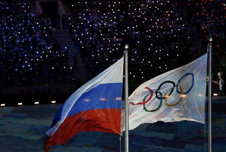 The Russian national flag flutters next to the Olympics flag during the closing ceremony for the 2014 Sochi Winter Olympics, February 23, 2014. REUTERS/Issei Kato