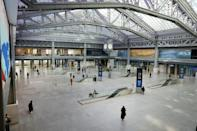 A handful of people walk through the largely deserted $1.6 billion new Moynihan Train Hall in Manhattan