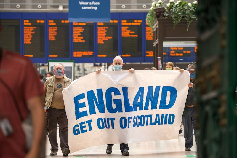 The protesters held up a banner that read 'England Get Out of Scotland' (Picture: SWNS)