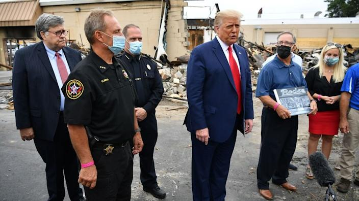 Mr Trump posed in front of a burned down camera shop with a man he wrongly claimed to be the business owner