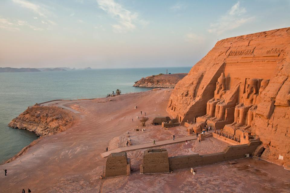 """The Abu Simbel Temples were built by Ramses II of the Nineteenth Dynasty of Egypt during his reign from 1279-13 B.C.E. The complex, in southern <a href=""""https://www.cntraveler.com/story/egyptian-tombs-open-to-public?mbid=synd_yahoo_rss"""" rel=""""nofollow noopener"""" target=""""_blank"""" data-ylk=""""slk:Egypt"""" class=""""link rapid-noclick-resp"""">Egypt</a>, includes two temples: both the Great Temple and nearby Small Temple. Carved out of a sandstone cliff, the Great Temple's main entrance is flanked by four statues of Ramses himself, with likenesses of family members at his feet. Supposedly, the structure is dedicated to the ancient sun gods Amon-Re and Re-Horakhte, though Ramses is also depicted as a god. On two days of the year—usually February 21 and October 21—the sun hits the Great Temple just right and illuminates the inner shrine."""