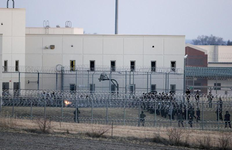Security forces in riot gear surround a courtyard behind razor wire at the Tecumseh State Correctional Institution in Tecumseh, Neb., Thursday, March 2, 2017, where dozens of inmates congregated after refusing to return to their cells. The prison was placed on lockdown for roughly three hours Thursday after inmates in a housing unit refused to return to their cells and a fire was started in a yard. (AP Photo/Nati Harnik)
