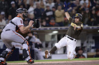 San Diego Padres' Ian Kinsler slides home before being tagged out by San Francisco Giants catcher Erik Kratz during the fifth inning of a baseball game Friday, March 29, 2019, in San Diego. (AP Photo/Orlando Ramirez)