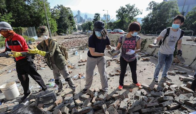Volunteers help clear a roadblock outside City University. Photo: May Tse