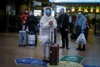 Travellers wear face masks at a train station following the outbreak of the coronavirus disease (COVID-19) in Beijing