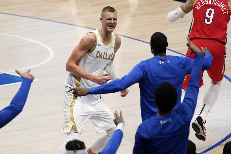 Players on the Dallas Mavericks bench celebrate a 3-point basket made by Kristaps Porzingis (6) during the first half of an NBA basketball game against the New Orleans Pelicans in Dallas, Friday, Feb. 12, 2021. (AP Photo/Tony Gutierrez)