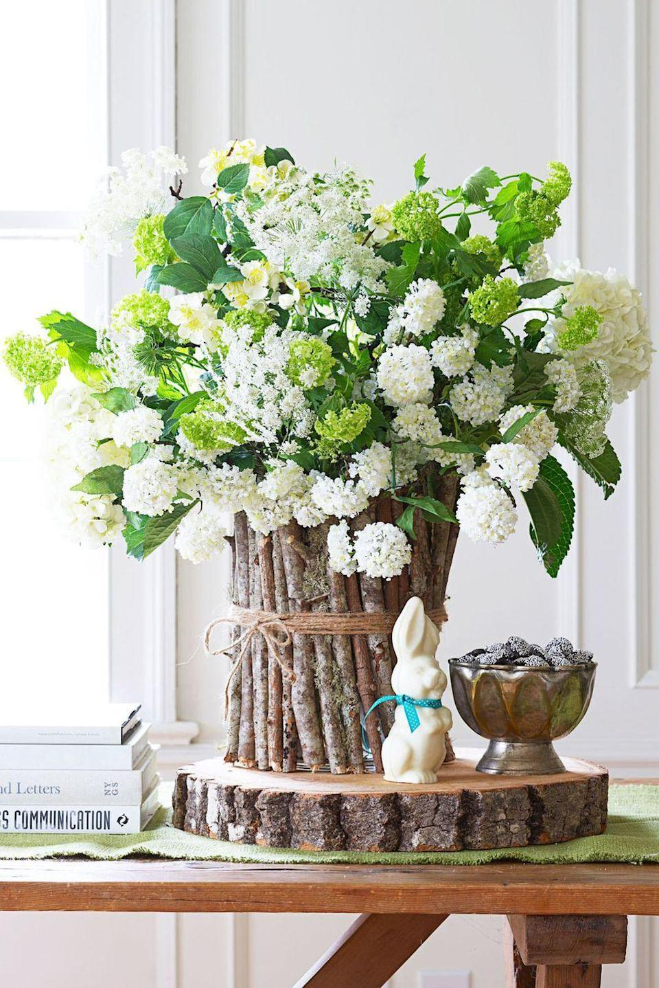 <p>A woodsy vase echoes these flowers' country-garden vibe. For the container, cut 30 to 40 twigs to the height of a glass vase, then glue them to its surface, a few inches at a time. Finish with jute twine tied in a bow. </p>
