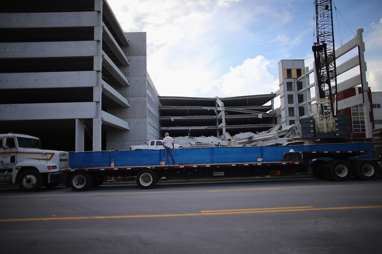 DORAL, FL - OCTOBER 10:  A construction worker looks on from a flat bed truck as Miami-Dade Fire Rescue search and rescue workers search in the rubble of a four-story parking garage that was under construction and collapsed at the Miami Dade College's West Campus on October 10, 2012 in Doral, Florida.  Early reports indicate that one person was killed, at least seven people injured and one is still trapped.  (Photo by Joe Raedle/Getty Images)