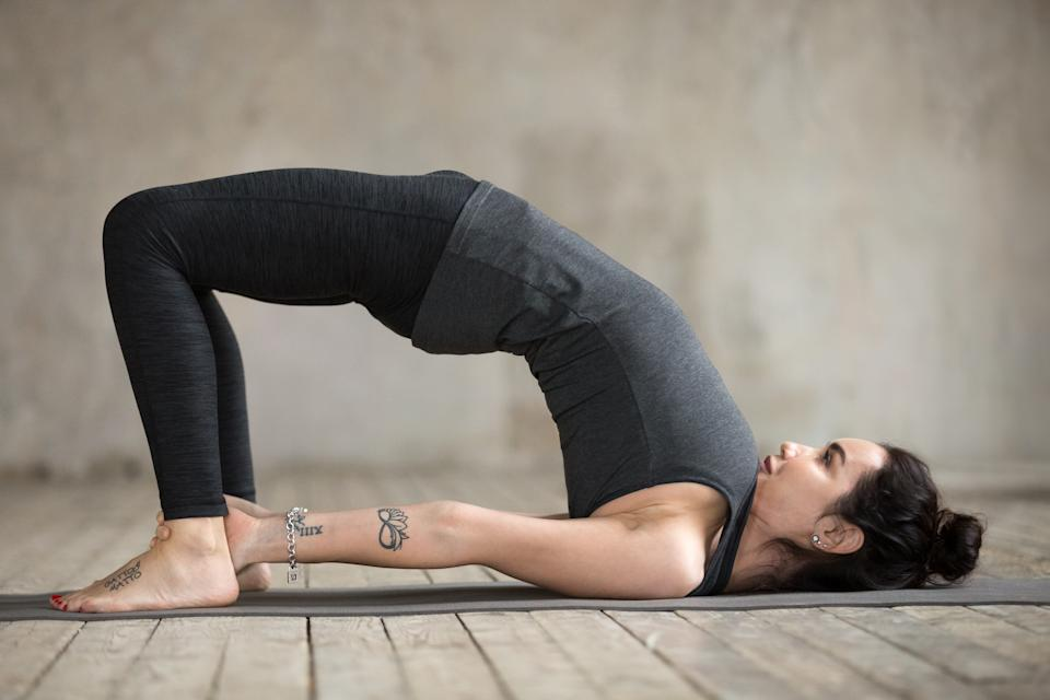 Young sporty woman practicing yoga, doing dvi pada pithasana exercise, Glute Bridge pose, working out, wearing sportswear, black pants and top, indoor full length, gray wall in yoga studio