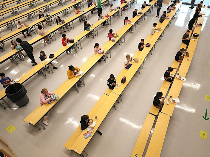 """Schoolchildren are spaced apart in one of the rooms used for lunch at Woodland Elementary School in Milford, Massachusetts. <p class=""""copyright"""">Suzanne Kreiter/The Boston Globe via Getty Images</p>"""