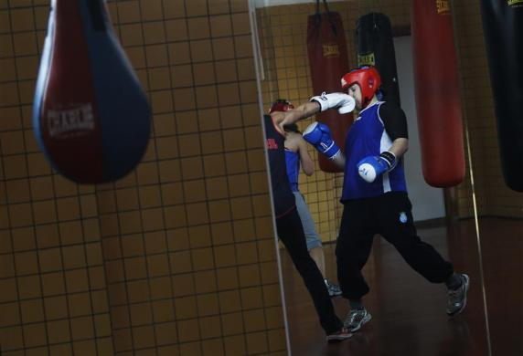 Argentine born boxer Tamara Fabiana Garcia gets punched in the face by fellow boxer Jennifer Miranda during a training session at a high-performance sports centre in Los Alcazares, southeastern Spain, April 2, 2012.