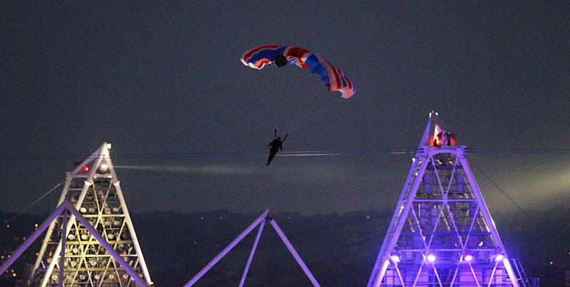 FILE In this July 27, 2012 file photo, British stuntman Mark Sutton, parachuting into the Olympic Stadium, dressed as James Bond, during the Olympic Games 2012 Opening Ceremony. The British stuntman who parachuted into the London Olympics opening ceremony as James Bond has been killed in an accident in the Swiss Alps while flying a special wing suit. Online extreme sports broadcaster Epic TV says Mark Sutton died during a gathering it had organized involving 20 wing suit pilots who were being filmed as they jumped from helicopters. Swiss police confirmed that a 42-year-old Briton died Wednesday, Aug. 14, 2013, in a fall near Trient in the Valais region. (AP Photo/PA, Lewis Whyld, File) UNITED KINGDOM OUT