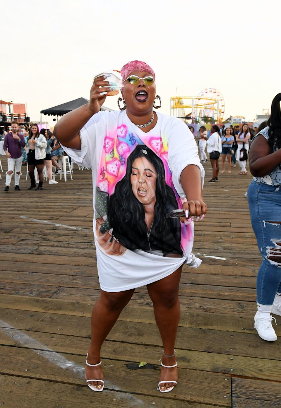 """Lizzo turned up to the JBL True Summer event on the world-famous Santa Monica Pier in a pink pixie cut and a T<a href=""""https://www.teenvogue.com/story/lizzo-t-shirt-face?mbid=synd_yahoo_rss"""" rel=""""nofollow noopener"""" target=""""_blank"""" data-ylk=""""slk:-shirt dress with her own face on it"""" class=""""link rapid-noclick-resp"""">-shirt dress with her own face on it</a>. Lizzo is clearly her own biggest fan, and we love it."""