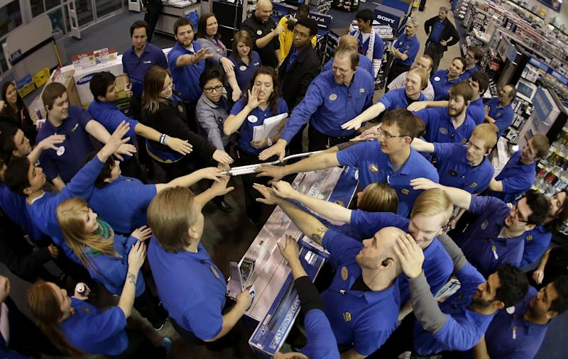 Best Buy employees rally after a pep talk as they prepare to open the store to shoppers Thursday, Nov. 28, 2013, in Overland Park, Kan. Instead of waiting for Black Friday, which is typically the year's biggest shopping day, more than a dozen major retailers are opening on Thanksgiving this year. (AP Photo/Charlie Riedel)