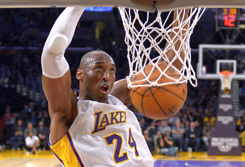 FILE - In this Jan. 4, 2015 file photo Los Angeles Lakers guard Kobe Bryant dunks during the first half of an NBA basketball game against the Indiana Pacers in Los Angeles. Bryant, a five-time NBA champion and a two-time Olympic gold medalist, died in a helicopter crash in California on Sunday, Jan. 26, 2020. He was 41. (AP Photo/Mark J. Terrill)
