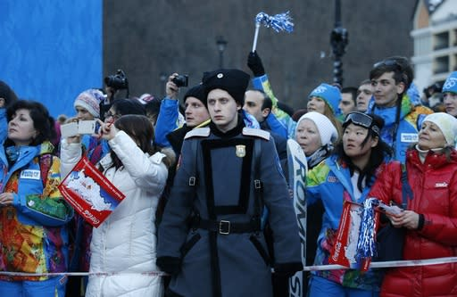 A Cossack stands on guard as people try to get a glimpse of the Olympic torch as it makes it's way throughout the streets of the Rosa Khutor ski resort in Krasnaya Polyana, Russia at the Sochi 2014 Winter Olympics, Wednesday, Feb. 5, 2014. (AP Photo/Christophe Ena)