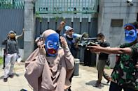 Indonesian student activists take part in a role-play as they demonstrate against alleged human rights abuses against China's Uyghur minority outside the Chinese embassy in Jakarta on March 25, 2021