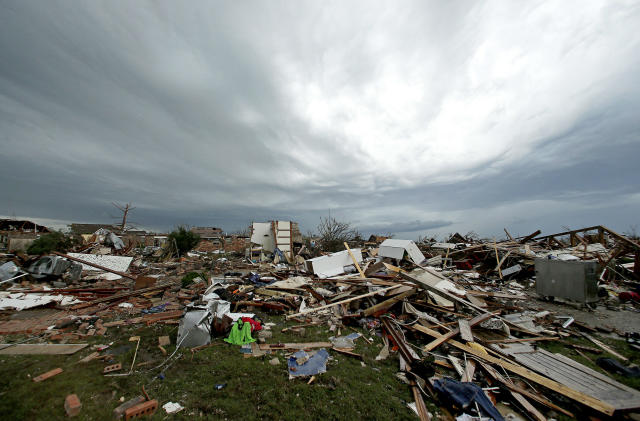 <p> Storm clouds build in the distance beyond tornado-ravaged homes Tuesday, May 21, 2013, in Moore, Okla. A huge tornado roared through the Oklahoma City suburb Monday, flattening entire neighborhoods and destroying an elementary school with a direct blow as children and teachers huddled against winds. (AP Photo/Charlie Riedel)</p>
