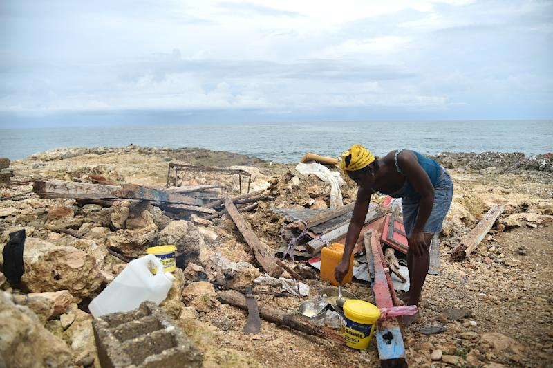 Leolien prepares food next what remains of her house destroyed by Hurricane Matthew in the neighborhood of Deye Distriyel in Jeremie, southwest Haiti, on October 23, 2016 (AFP Photo/Hector Retamal)