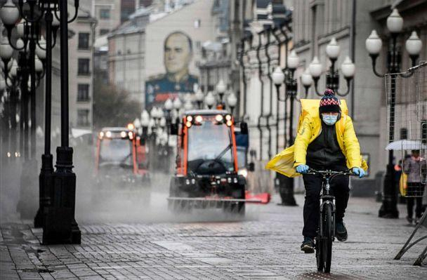 PHOTO: A food delivery courier cycles along pedestrian Arbat street as municipal vehicles clean and disinfect the area, in downtown Moscow, Russia, on April 14, 2020. (Alexander Nemenov/AFP via Getty Images)