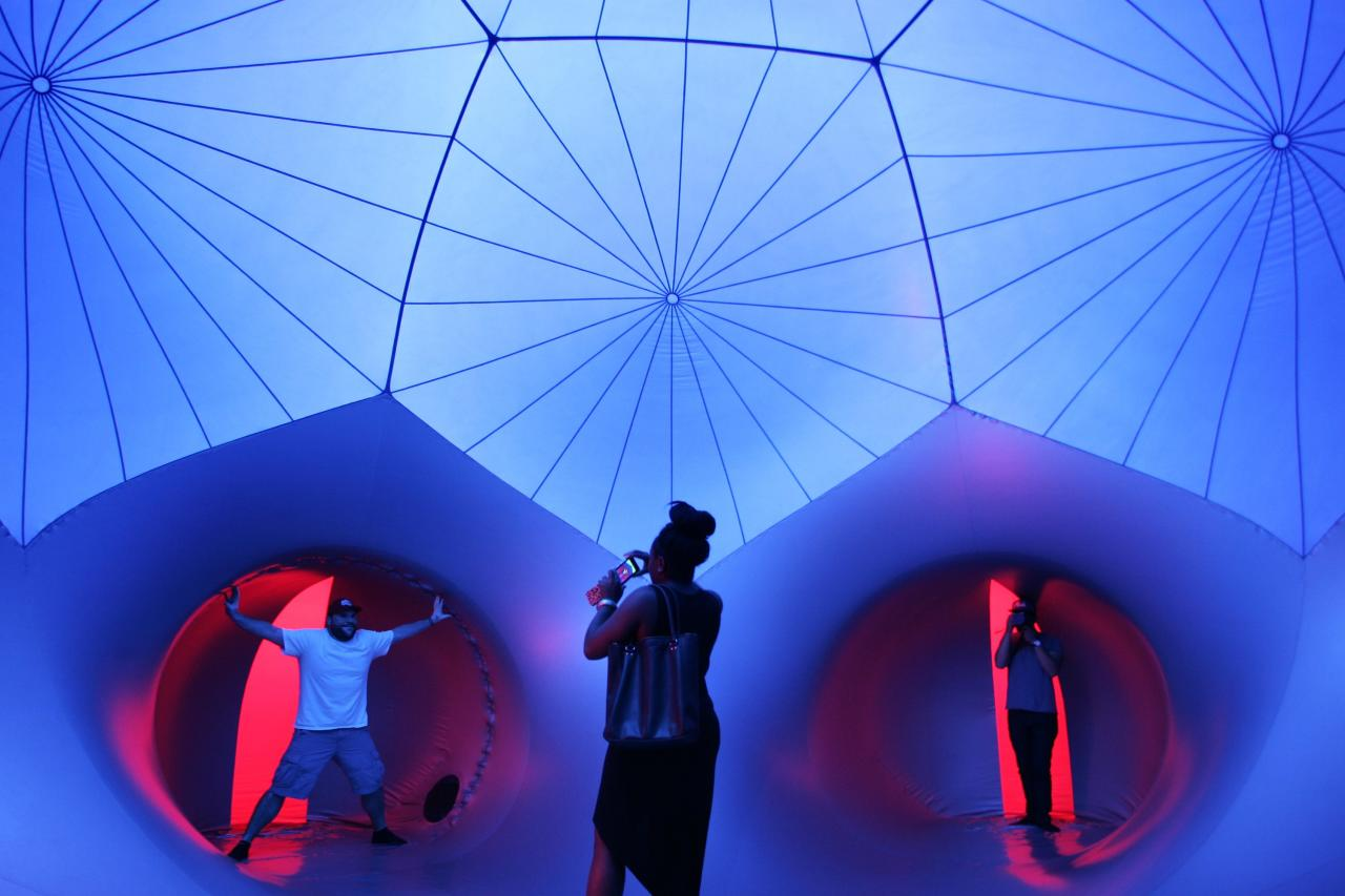 People walk through Exxopolis, an inflatable walk-in luminarium at Grand Park in Los Angeles, California, September 7, 2013. The inflatable walk-in luminarium, designed by Architects of Air, creates a maze of winding paths and domes featuring Islamic architecture, Archimedean solids, and Gothic cathedral designs. REUTERS/Jonathan Alcorn (UNITED STATES - Tags: SOCIETY)