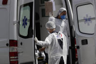 FILE - In this April 14, 2021, file photo, healthcare workers exit an ambulance carrying a patient suspected of having COVID-19 as they arrive at the HRAN public hospital in Brasilia, Brazil. The picture is still grim in parts of Europe and Asia as variants of the virus fuel an increase in new cases and the worldwide death toll closes in on 3 million.(AP Photo/Eraldo Peres, File)