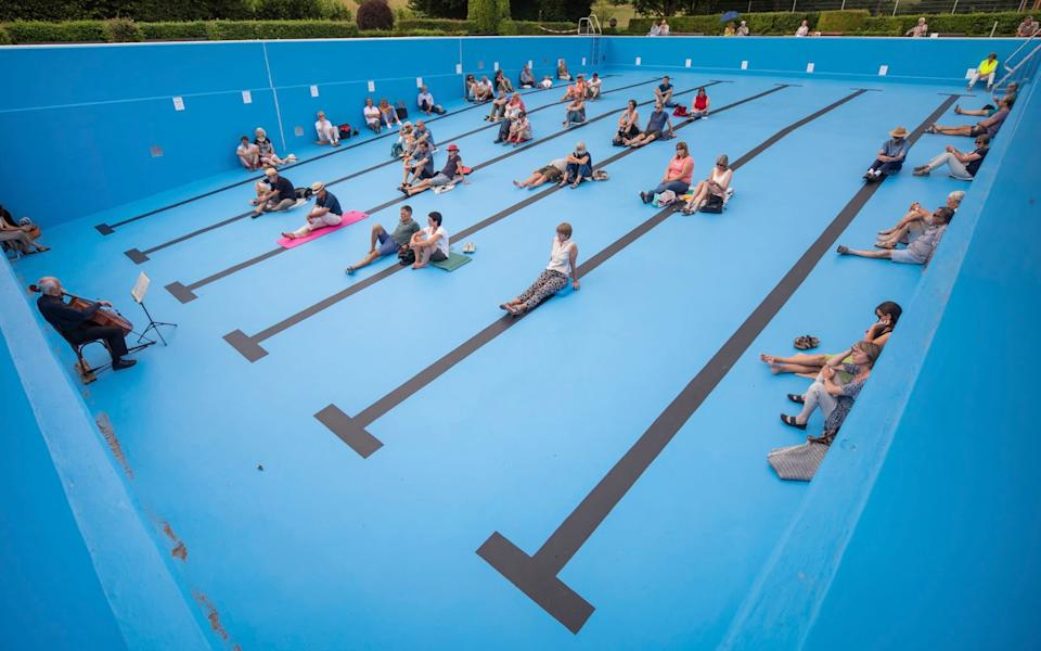 Visitors watch a cello concert by J'rgen Gerlinger performed in an empty outdoor swimming pool, in Entringen, Germany yesterday - Christoph Schmidt/dpa via AP
