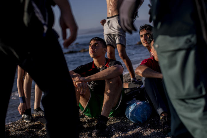 Surrounded by Spanish civil guards, migrants sit on the beach after arriving at the Spanish enclave of Ceuta, near the border of Morocco and Spain, Wednesday, May 19, 2021. (AP Photo/Bernat Armangue)