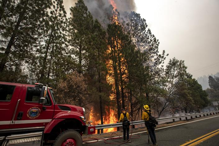 """Flames consume dry brush around Santa Barbara city firefighters Eric Cole, left, and Mark Kramer as the crew sets a backfire along Oro Quincy Highway in the aftermath of the Bear fire on Thursday, Sept. 10, 2020, in Oroville, Calif. <span class=""""copyright"""">(Brian van der Brug / Los Angeles Times)</span>"""