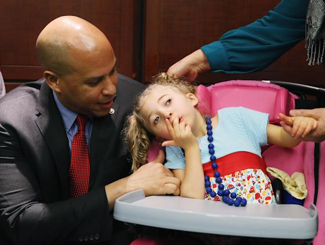 Sen. Cory Booker comforts 4-year-old Morgan Hintz, who suffers from a rare form of epilepsy, during a news conference on medical marijuana. (Photo: Mark Wilson/Getty Images)