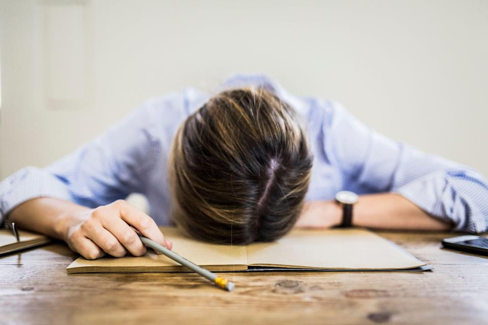 Close-up of woman lying on notebook at desk